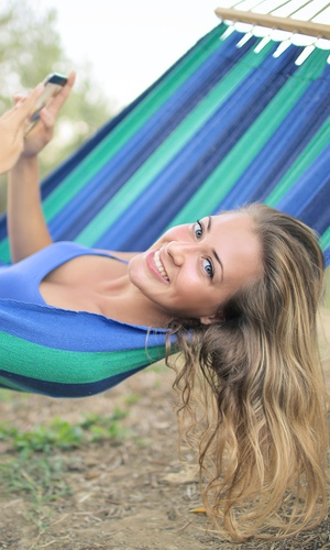 cheerful lady relaxing in a hammock